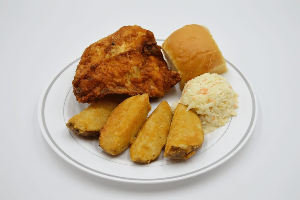 plate of fried chicken, potato wedges, coleslaw, and a dinner roll