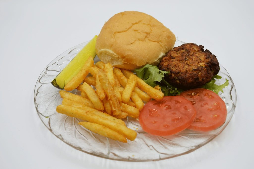 crab cake with french fries and a pickle spear