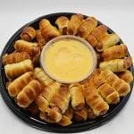 platter of pretzel wrapped hot dogs and cheese dip