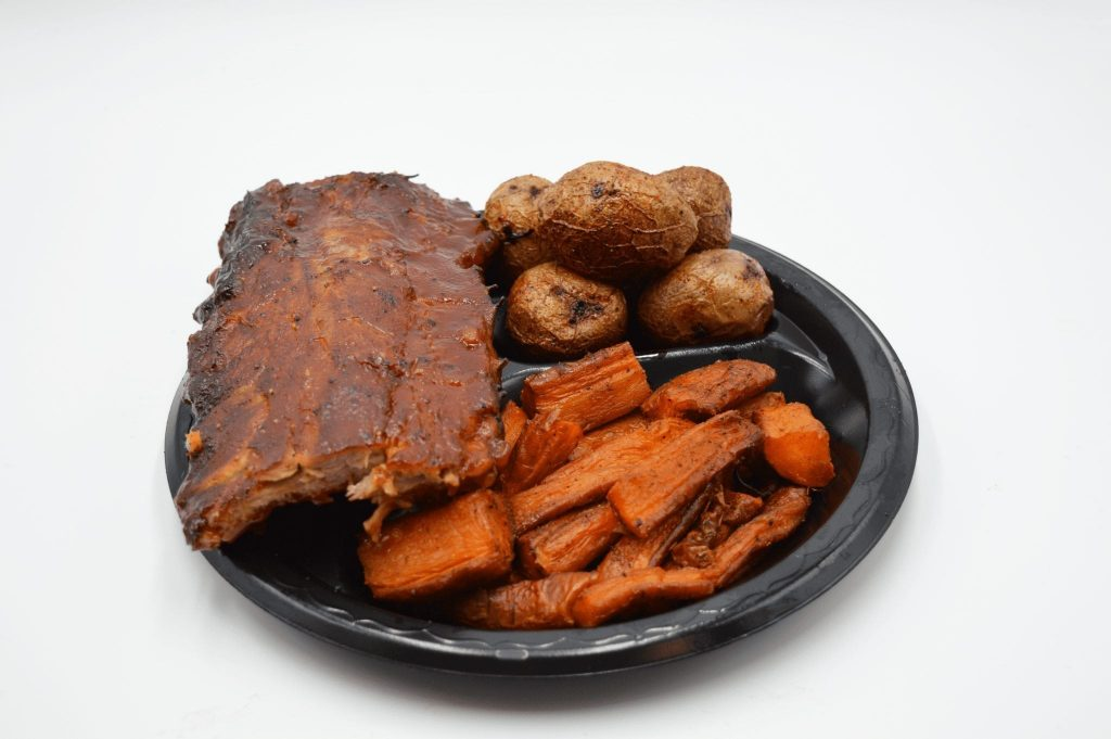 plate containing BBQ ribs, carrots, and potatoes